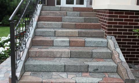 Стильное крыльцо коттеджа: натуральный камень на ступенях и кованые перила