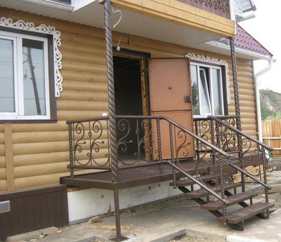 Металлическое крылечко у входа в деревянный дом