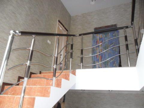 Бетонная лестница, отделанная плиткой и украшенная металлическими перилами