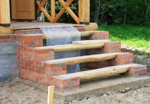 Бетонный фундамент, кирпичное основание и деревянное крыльцо дома