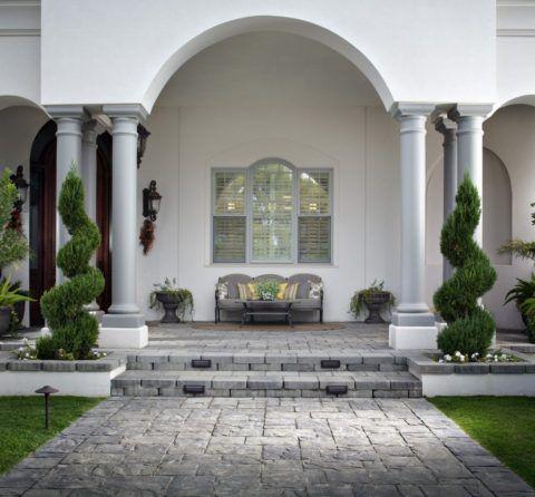 Крыльцо, отделанное бетонной плиткой, прекрасно смотрится вместе с серыми колоннами на белых тумбах