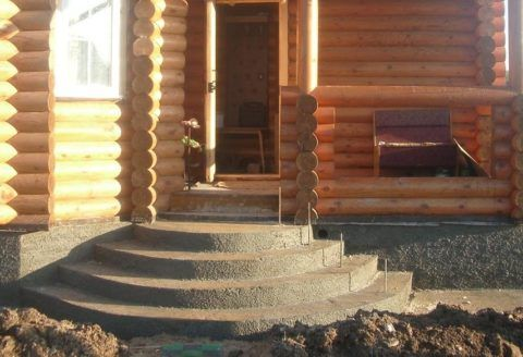 Полукруглое бетонное крыльцо к деревянному дому