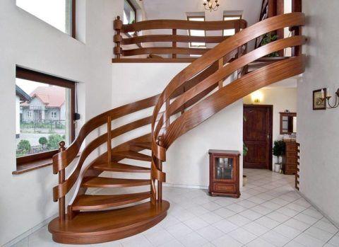 Спиралевидная конструкция деревянной лестницы, покрытой лаком