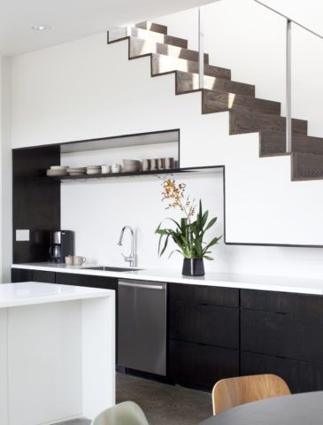 В задуманный стиль всего интерьера помещения можно прекрасно вписать и кухонную мебель под лестницей