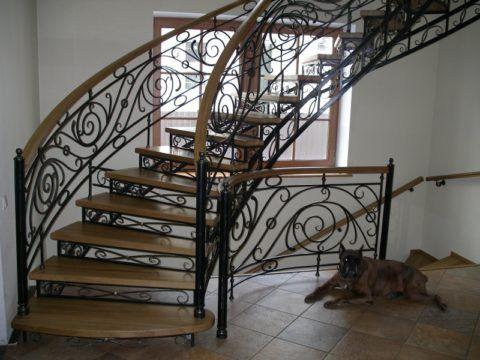 Винтовая кованая лестница с деревянными ступенями и поручнем