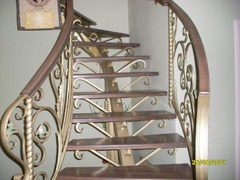Винтовая кованая лестница с каркасом на центральном косоуре