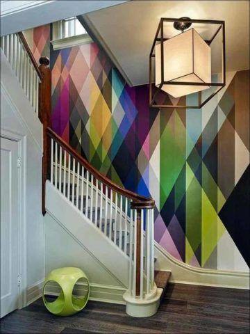 Выделить лестницу в интерьере можно, оформив в яркие цвета свободную стену