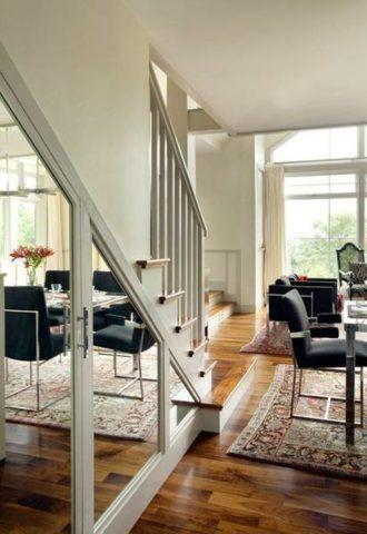 Зеркальные поверхности дверец, встроенного в лестницу шкафа, зрительно увеличивают окружающее пространство