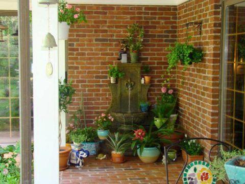 Композиция из живых растений и фонтан для декорирования площадки крыльца