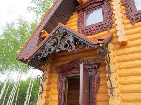 Кованый козырек на деревянном фасаде отлично гармонирует с резными наличниками
