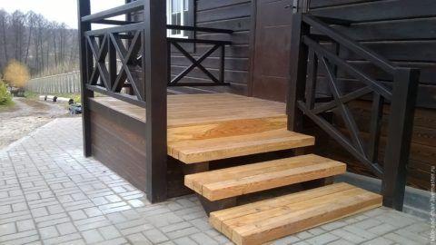 Деревянное крыльцо с перилами и небольшой верхней площадкой
