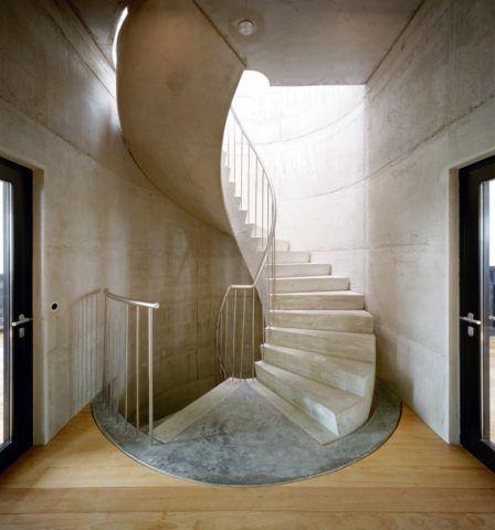 Из монолитного бетона можно создать любую конфигурацию: отделка внутренней лестницы и стен штукатуркой с эффектом бетона