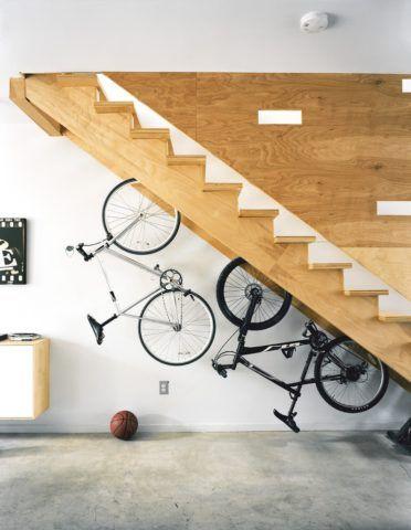 Лестница в интерьере коттеджа с вешалкой для велосипедов на оборотной стороне ступеней