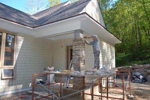Процесс облицовки камнем столба, выложенного из бетонных блоков