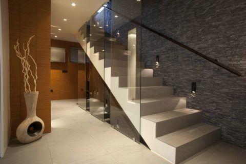 Современный интерьер: стены вдоль лестницы сделаны под камень и оснащены точечными светильниками