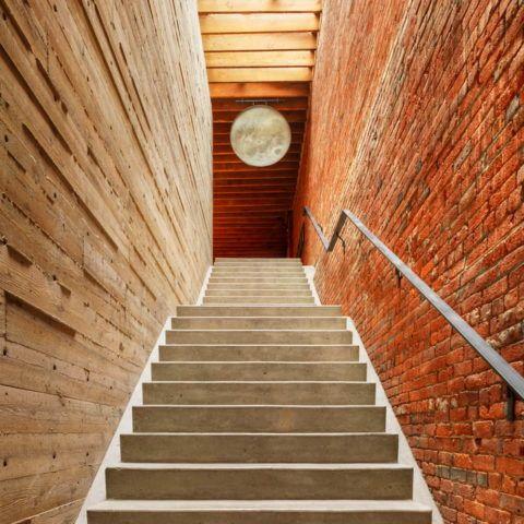 Бетонная лестница между кирпичной и деревянной стеной – прекрасное сочетание материалов, возможное, пожалуй, лишь в стиле лофт