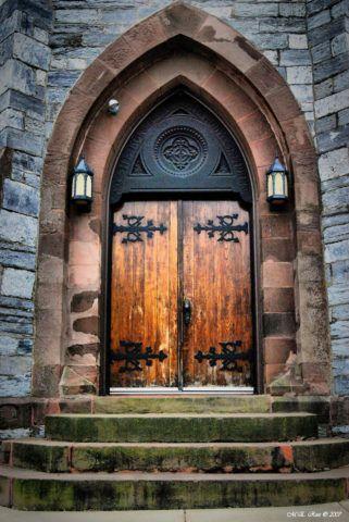 Деревянные полотна двери в готическом стиле устроены на металлических кованных петлях