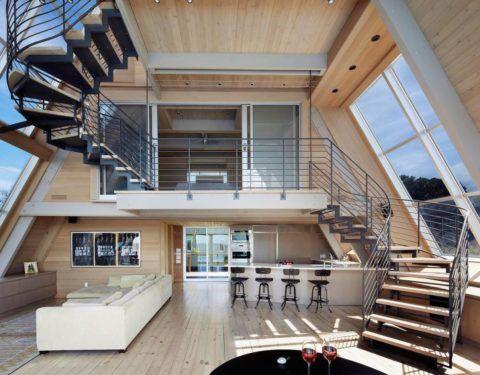 Интерьер частного дома с панорамным освещением, где лестница является главным акцентом