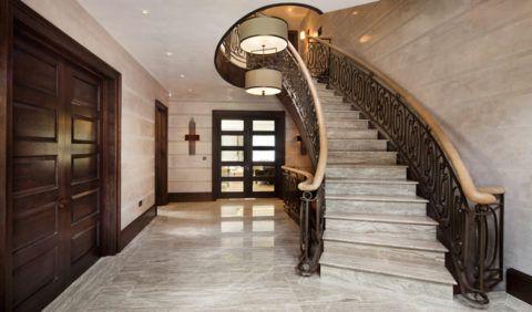 Использование натурального дерева, металла и светлого мрамора в отделке пола и лестницы входного холла частного дома