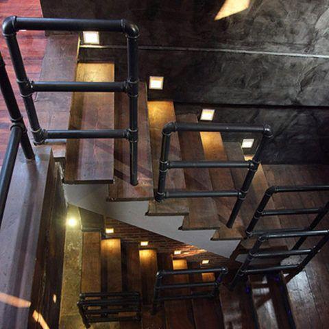 Металлические перила для лестницы изготовлены из круглой трубы с имитацией водопроводных коммуникаций