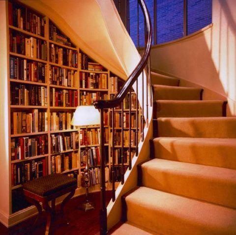 Подлестничное пространство спиральной лестницы отлично подойдет для размещения библиотеки