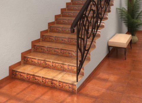 Терракотовая фронтальная плитка для ступеней и подступенки с цветочным орнаментом прекрасно сочетаются с коваными металлическими перилами