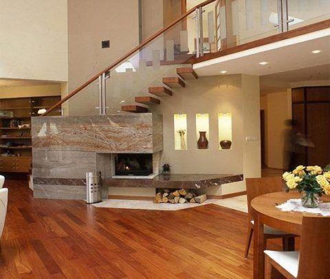 Удачное устройство каменного встроенного камина под лестницей в стиле хай-тек
