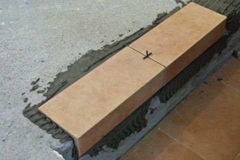 Угловая плитка закрывает часть проступи и подступенка, защищая кромку ступени
