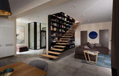 Дизайн гостиной с лестницей на второй этаж на центральном косоуре