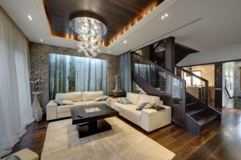 Интерьер гостиной в частном доме с лестницей в современном стиле