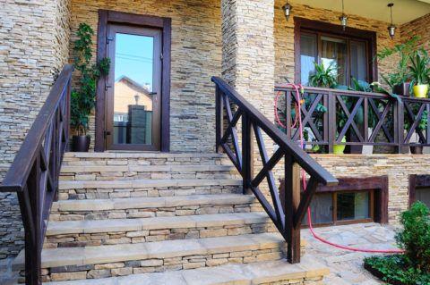 Лестницы и ограждения в коттеджах выполняют из сочетаемых материалов, например, натурального камня и древесины