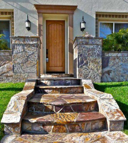 Массивное крыльцо из натурального камня гармонично сочетается с ограждением