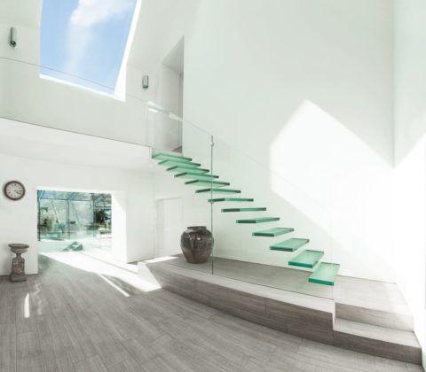 Особенно легкой и невесомой воспринимается одномаршевая лестница со ступенями из каленого стекла, закрепленными на больцы