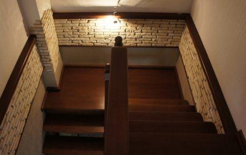 Отделка лестничного пространства камнем и деревом