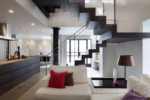 Свободная планировка современного частного дома с лестницей в гостиной
