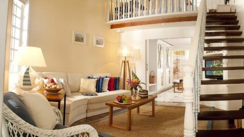 В небольшой гостиной можно установить узкую лестницу с белыми перилами и сквозными ступенями, чтобы она смотрелась легче