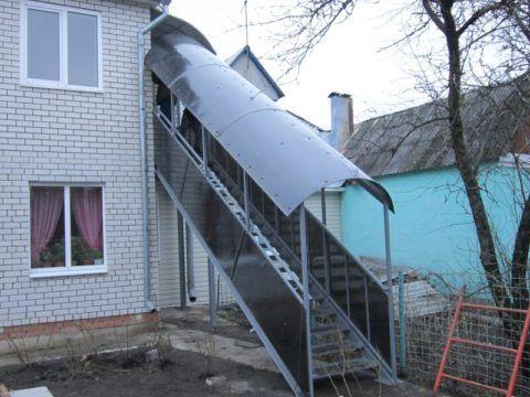 Наружная металлическая лестница на второй этаж с навесом – не слишком красиво, но практично