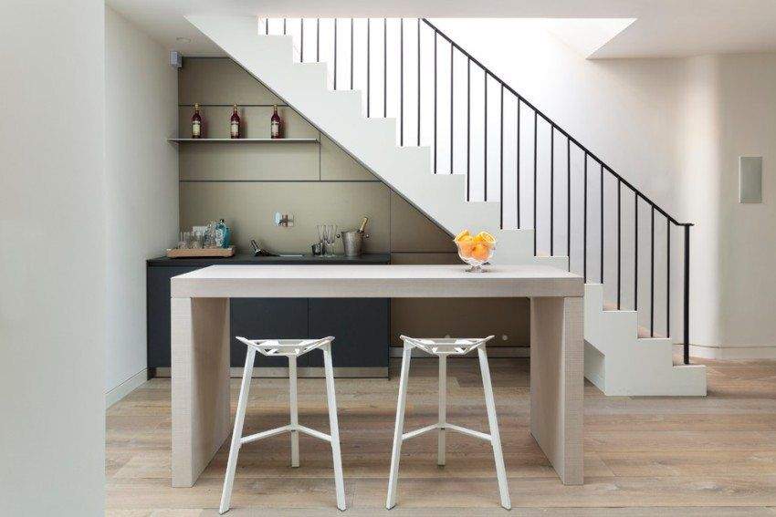В условиях ограниченной площади пространство под лестницей можно использовать под кухню