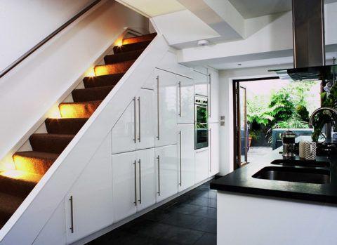 Не обязательно размещать под ступенями кухню. Это место отлично подойдет для установки бытовых приборов и шкафов для хранения