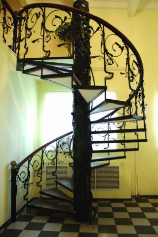 На фото кованые перила винтовых лестниц хорошо сочетаются с такой же центральной осью