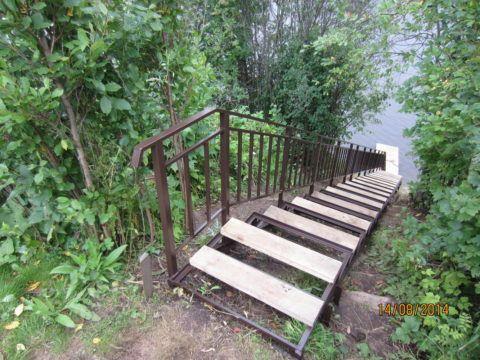 Металлическая лестница к пруду с пристанью