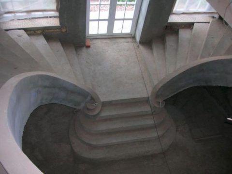 На фото изящная монолитная лестница без декоративной отделки выглядит серо и уныло