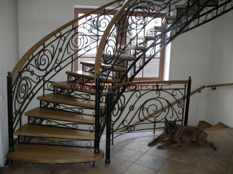 Винтовая деревянная лестница с коваными перилами