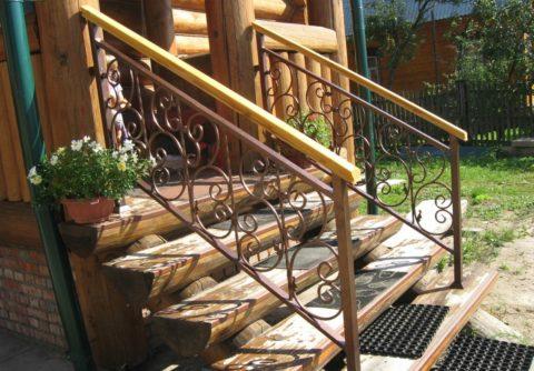 Металлическое ограждение бревенчатой лестницы