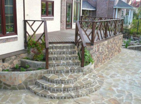 Бетонное крыльцо, в отделке которого использован натуральный камень и дерево