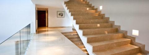На фото отделка камнем стены у лестницы – плинтус выпускается в составе коллекции